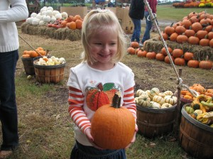Raegan and her very own pumpkin... which matches her shirt!