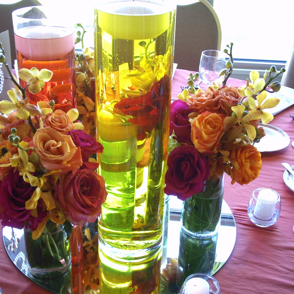 Here's a different idea, colored water in cylinder vases with floating candles, and then an empty cylinder to add the aisle clusters into.  I think that this is similar to the scale for your aisle arrangements, 4 to 5 roses, maybe one hydrangea, possibly with a green cym.