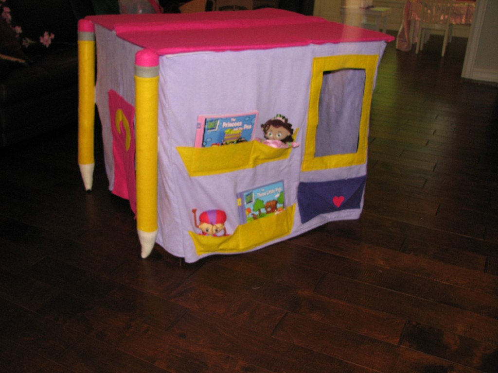 Card Table tents are all over etsy right now.  This side has pockets to hold books like the book club, and her little Super Why dolls.  Plus a pocket to hold letters!  And a window, which Serenity likes to use as a door.