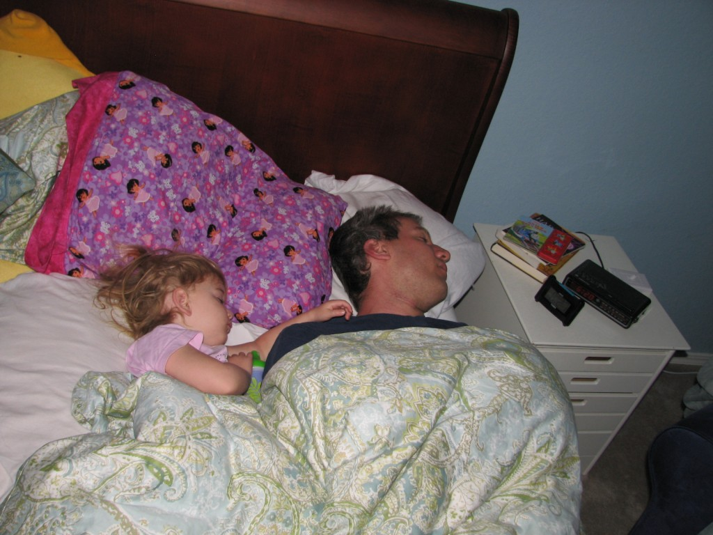My sleepy family =)  Eric is just barely hanging onto the bed... mostly the fault of my pillow tower.