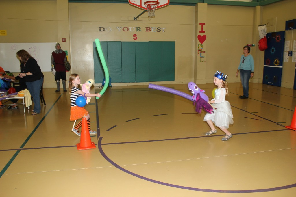 Serenity jousting with her friend Lillyan.  They were trying to knock balloons off their opponent's arms.  So much fun!!
