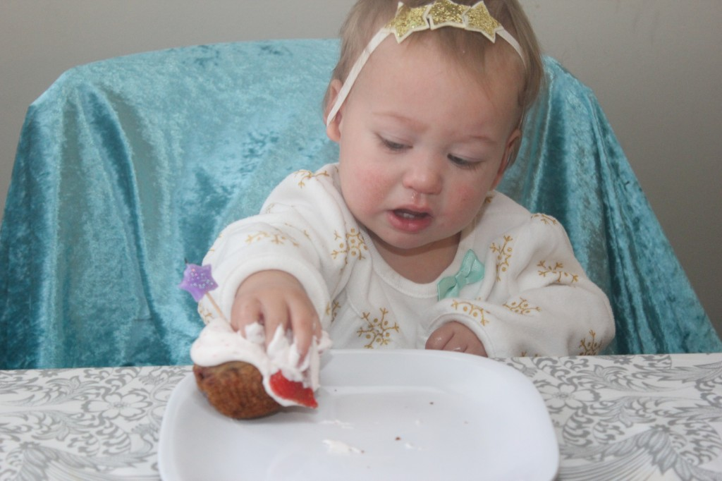 Strawberry muffin from her breakfast on her actual birthday.  =)  She was very interested in the feel of the whipped cream but didn't figure out it was food until I broke up the muffin for her.  She was trying to get the berry!