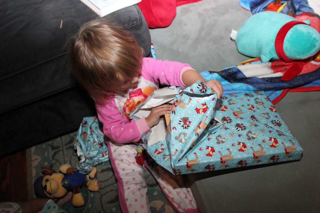 "Maia opens presents now!  And says ""THANKS!""  Sounds more like ""danks"" but it's there =)  A good week to learn that!"
