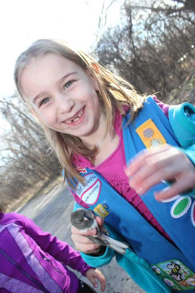 Holding a bird during a birding activity for Girl Scouts